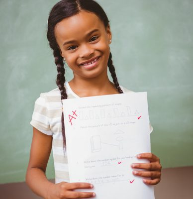 young girl holding a paper with an A+ grade